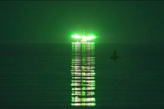 Ces lumières proviennent donc de bateaux de pêche qui utilisent d'énormes structures de LED qui diffusent des lumières vertes pour attirer les calmars et les planctons à la surface. crédit photo: gurumed.org/
